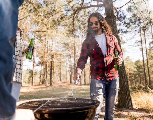Uomo che si prende cura del barbecue sorseggiando una birra