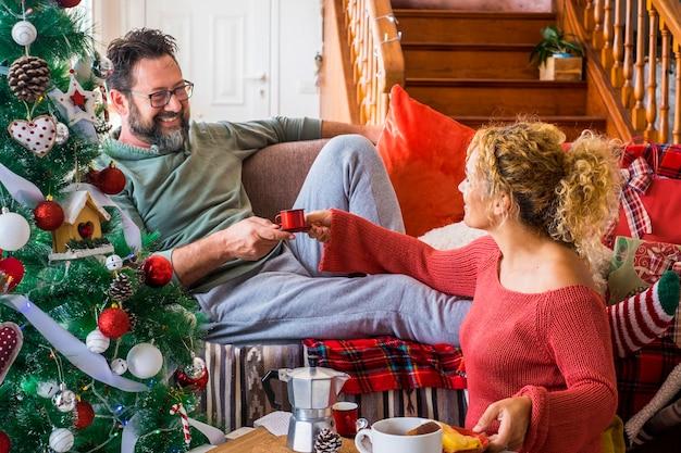 自宅でクリスマスのお祝いの間に彼の妻からコーヒーカップを取る男。クリスマスのお祝いの前夜に朝食をとる白人カップル。飾られたクリスマスツリーとリビングルームのカップル。
