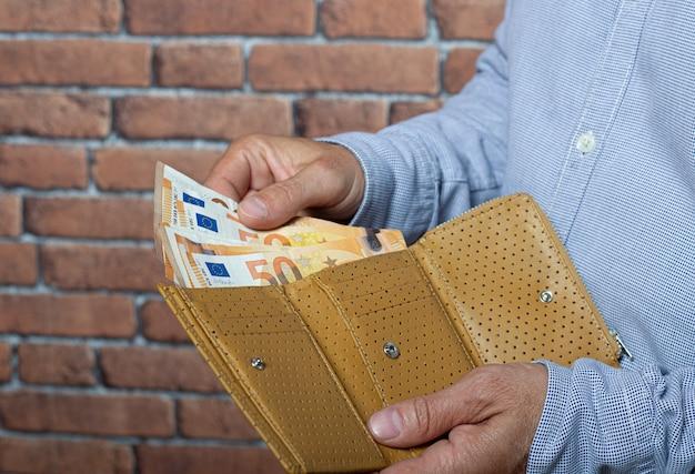 ポケットの財布からユーロのお金を取り出している男。
