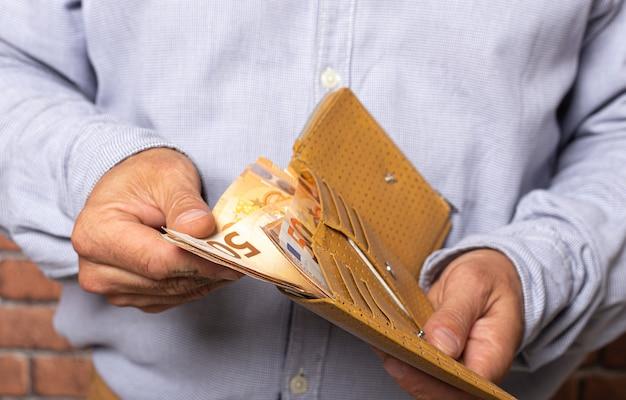 Человек берет деньги евро из своего карманного бумажника.