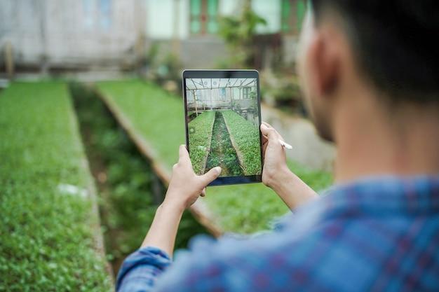 디지털 태블릿 디지털 농업 사진 개념을 사용하여 농장 사진을 찍는 남자