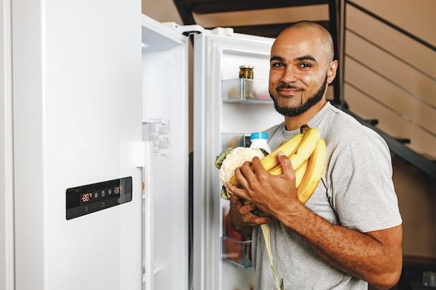 Мужчина берет еду из холодильника в своем доме