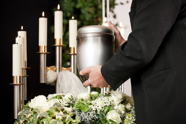 Man taking funeral urn with candles and flowers
