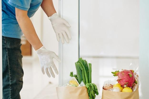 현관에서 식료품 가방을 복용하는 사람