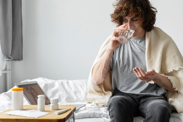 Man taking his pills in bed