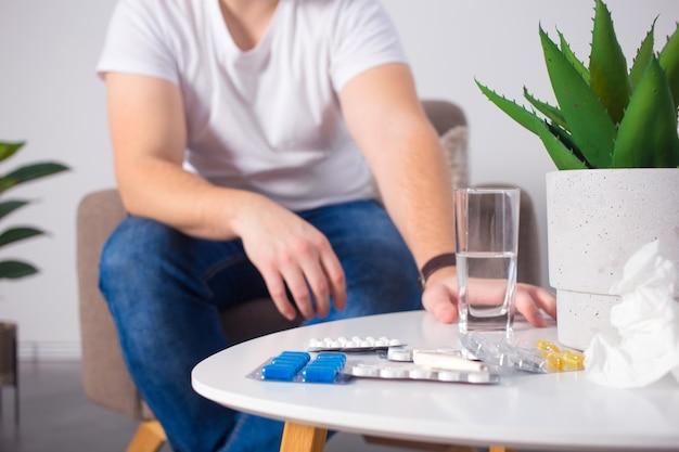 Человек принимает таблетки на диване в гостиной