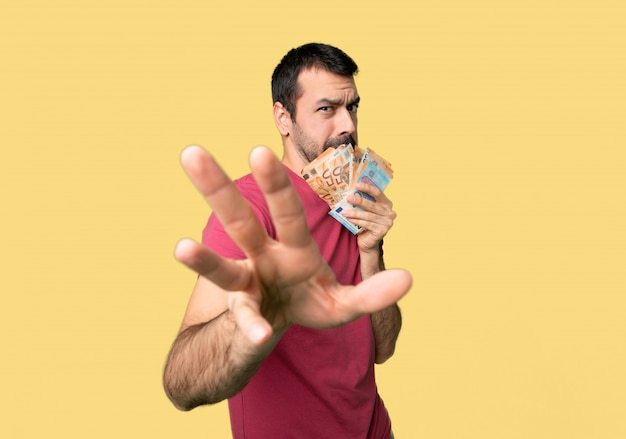 Man taking a lot of money is a little bit nervous and scared stretching hands to the front on isolated yellow background