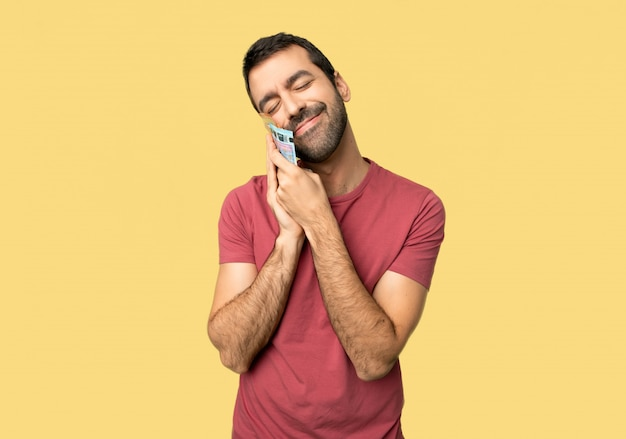 Man taking a lot of money making sleep gesture in dorable expression on isolated yellow background