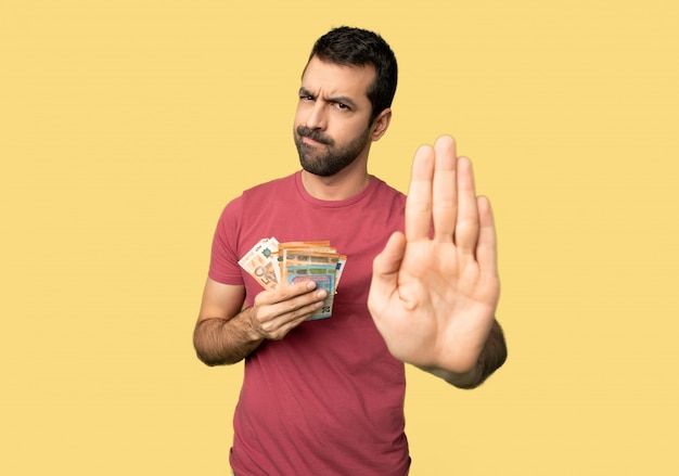 Man taking a lot of money making stop gesture denying a situation that thinks wrong on isolated yellow background