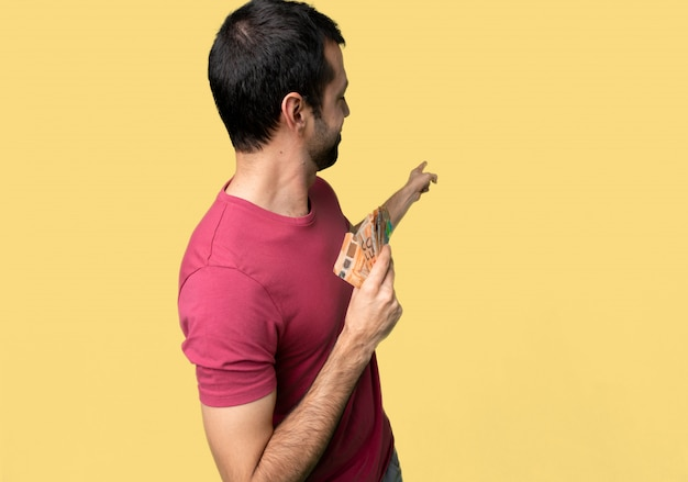 Man taking a lot of money pointing back with the index finger on isolated yellow background