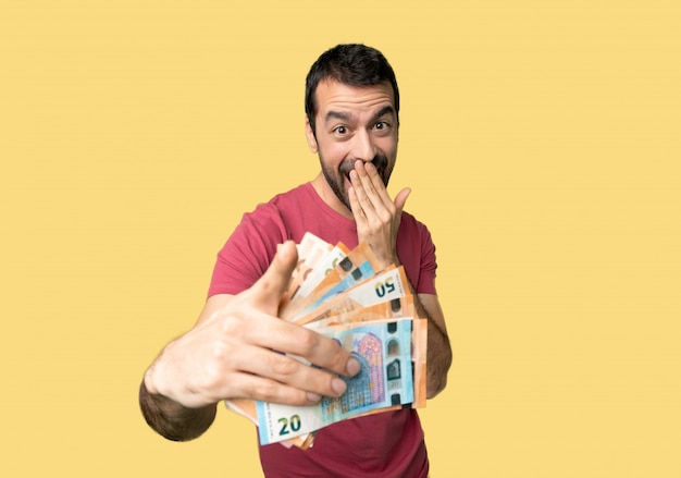 Man taking a lot of money pointing with finger at someone and laughing
