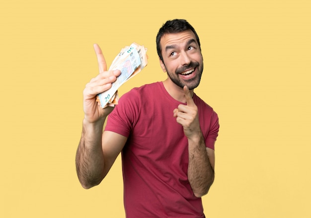 Man taking a lot of money pointing with the index finger and looking up on isolated yellow background