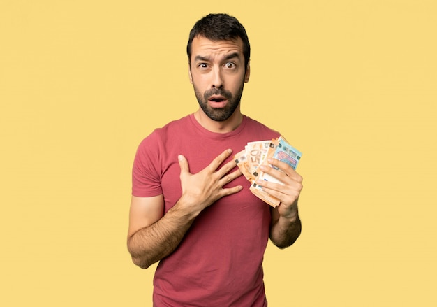 Man taking a lot of money surprised and shocked while looking right on isolated yellow background