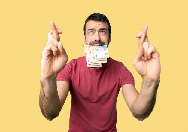 Man taking a lot of money with fingers crossing and wishing the best on isolated yellow background