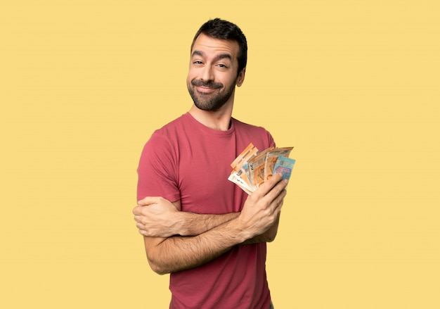 Man taking a lot of money with happy expression on isolated yellow background