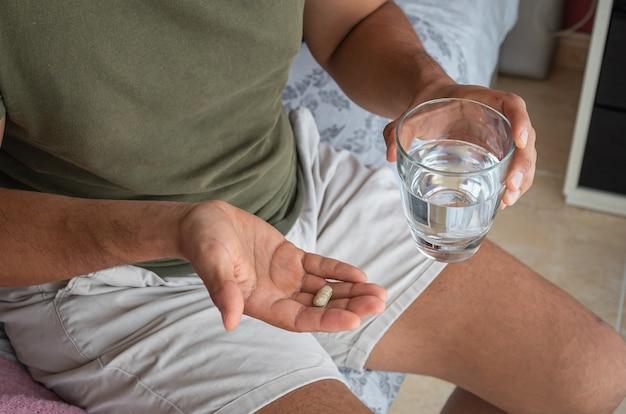 Man taking a melatonin pill to help him sleep. concept of sleep problems or insomnia