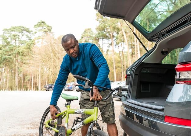Мужчина снимает велосипед с машины