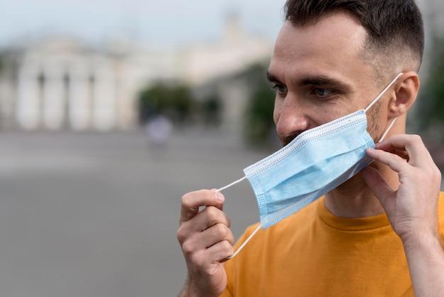 Мужчина снимает медицинскую маску на открытом воздухе