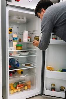 Man taking olive pickle from refrigerator