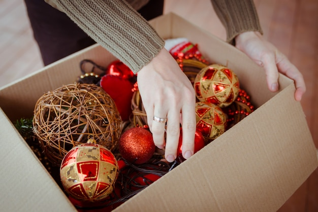 A man taking out a christmas ball from the cardboard box with toys for christmas tree ornaments
