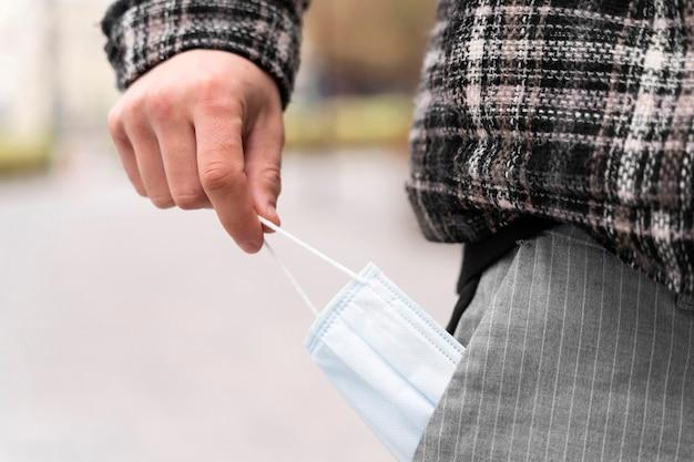 Человек вынимает из кармана медицинскую маску крупным планом
