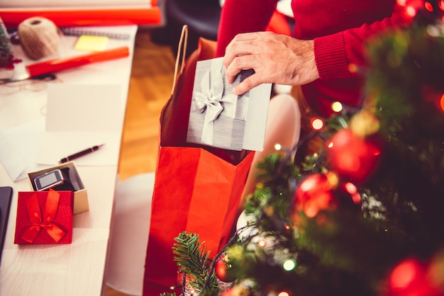 Man taking out present from a shopping bag