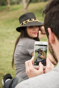 Man taking photo of her girlfriend from cell phone in the park
