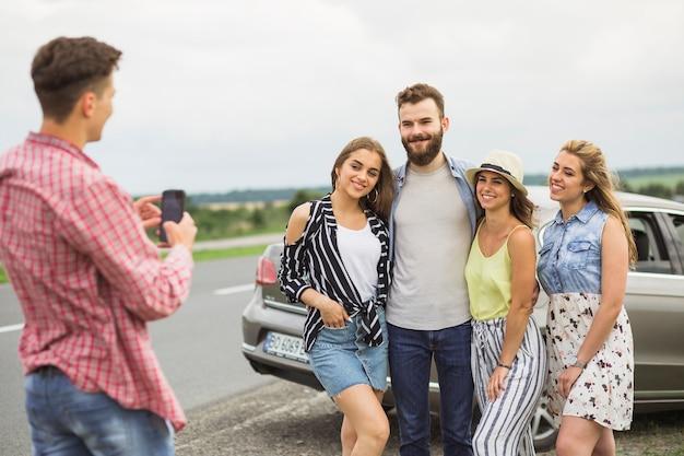 Uomo che cattura foto dei suoi amici sulla strada