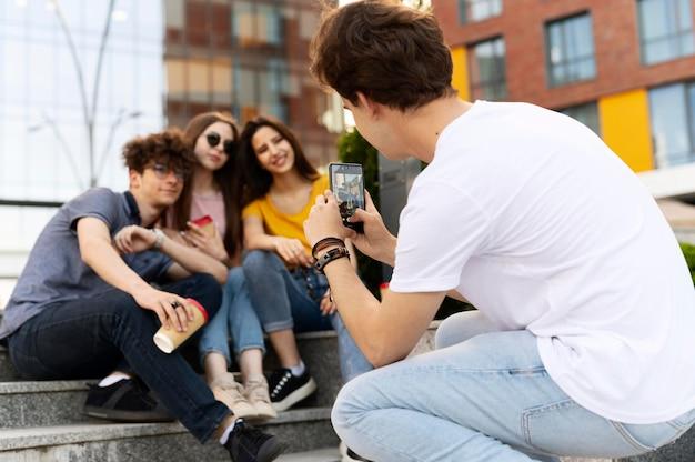 Uomo che scatta foto dei suoi amici mentre è all'aperto