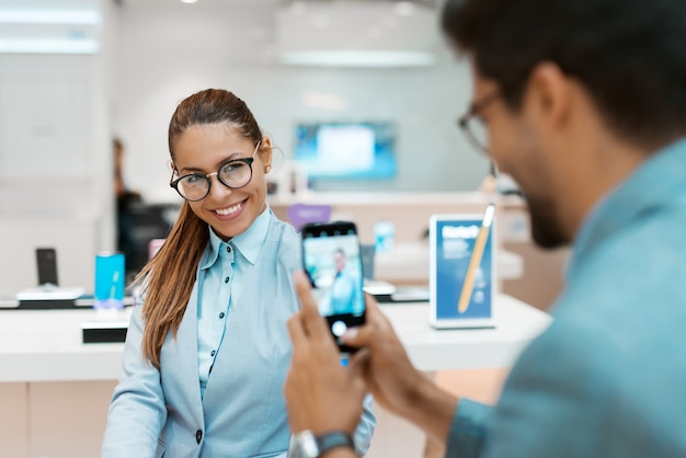 Man taking photo of his wife while standing in tech store. selective focus on woman.
