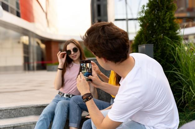 屋外で友達の写真を撮る男