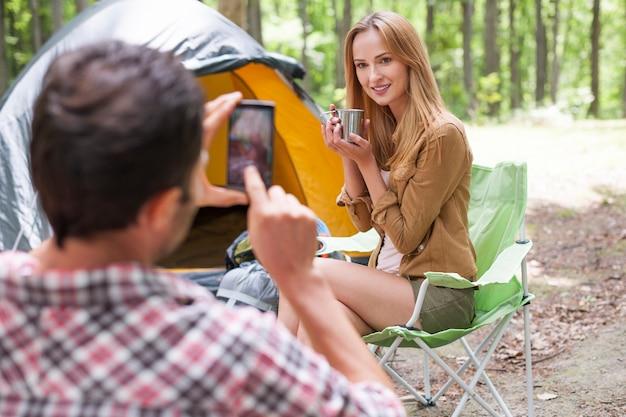 Человек фотографирует свою девушку в лесу