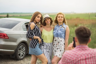 Man taking photo of three female friends standing near the car