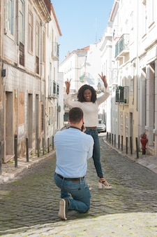 Man taking photo of playful black woman outdoors