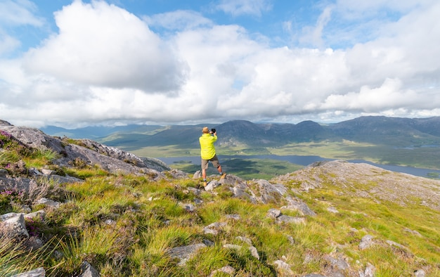 Man taking the photo shot in the connemara mountains, enjoying the view.