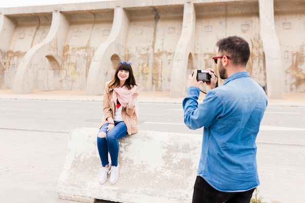 Man taking photo of smiling woman gesturing