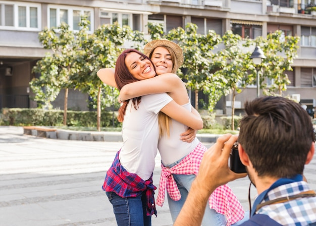Man taking photo of two female friends embracing each other