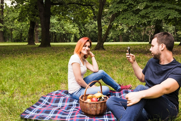 Man taking photograph of her smiling girlfriend on smartphone at picnic