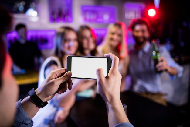 Man taking photograph of his friends with mobile phone