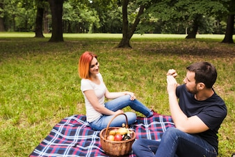 Man taking photograph of her girlfriend on cell phone at picnic