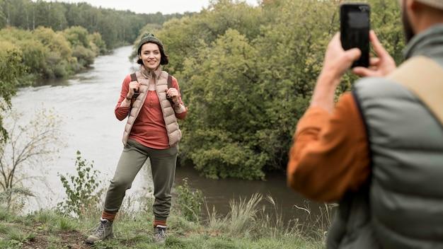 Uomo che cattura foto della ragazza in natura con lo smartphone