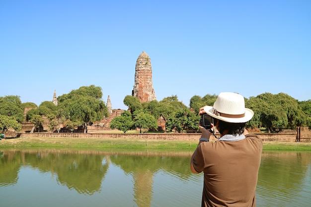 아유타야 역사 공원 태국에서 왓 프라 람 사원 유적의 중세 prang의 사진을 찍는 남자