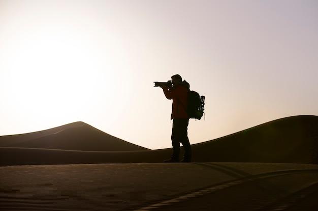 砂漠の日の出の写真を撮る男