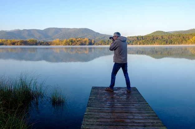 Man taking photos standing on a pier