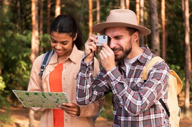 彼のガールフレンドが地図をチェックしている間に写真を撮る男