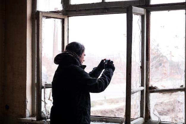 추운 겨울 날에 Abondened 건물 방 안에서 자신의 휴대폰으로 사진을 찍는 남자 프리미엄 사진