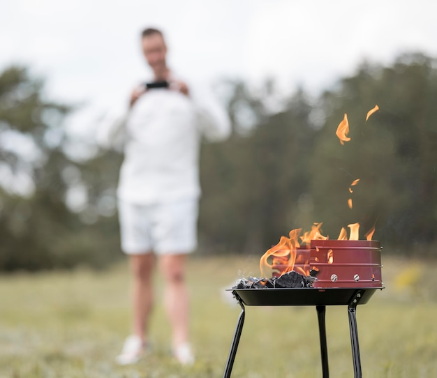 Man taking picture of barbecue outdoors