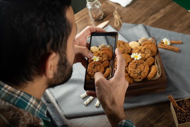 Man taking picture of cookie tray with his smartphone
