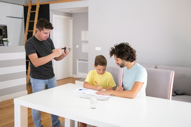 Man taking picture of cute son and husband doing school home task, writing or drawing in papers. family and gay parents concept