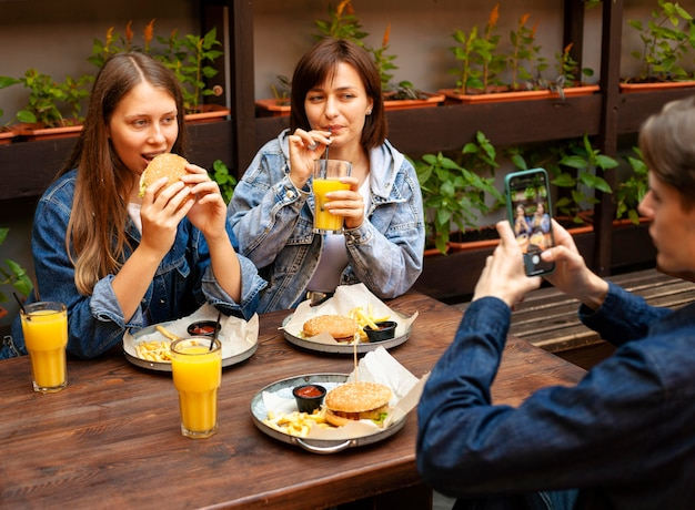 Man taking picture of female friends eating burgers